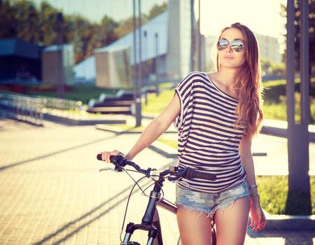도시 배경에 자전거와 트렌디 한 소식통 소녀. 톤 여과 사진. 현대 청소년 라이프 스타일 개념입니다.