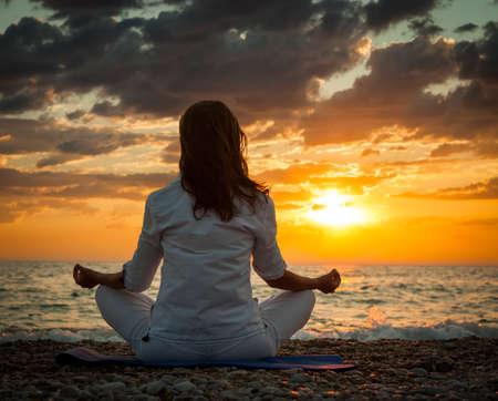 해질녘 바다로 요가 연습을하는 여자. 배면도. 극적인 하늘입니다. 건강 한 라이프 스타일 개념입니다. 스톡 콘텐츠