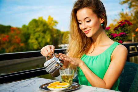 mujer alegre: Mujer joven que hace el t� verde al aire libre. Fondo de verano. Poca profundidad de campo.