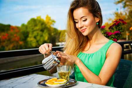 cute lady: Young Woman Making Green Tea Outdoors. Summer Background. Shallow Depth of Field.
