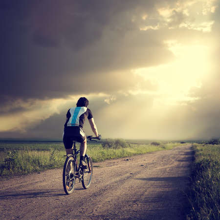 Epic Photo of Cyclist on the Country Road. Rear View. Dramatic Sky Background. Hope for Better Future Concept