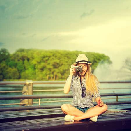 젊은 소식통 소녀 빈티지 카메라와 함께 사진을 만들기의 초상화. 현대 청소년 라이프 스타일 개념입니다.