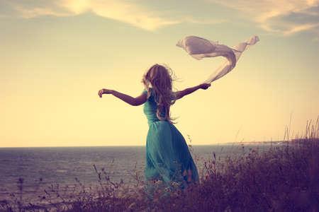 the farewell: Foto de la vendimia de la mujer rubia con la bufanda en el mar. Foto entonada con espacio de copia. Solitario. Foto de archivo