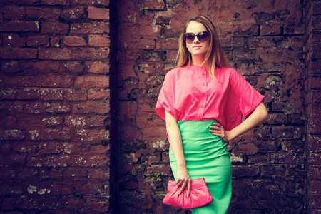 오래 된 벽돌 벽 배경에 서있는 아름 다운 유행 여자입니다. 도시의 패션 개념. 복사 공간 톤의 사진.