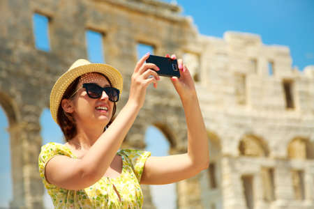 Beautiful Young Woman Taking Photo of Ancient Roman Arena in Pula with Her Smartphone. Travel and Vacation in Croatia. Stock Photo