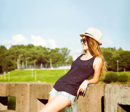 Trendy Hipster Girl Relaxing in the Park. Toned and Filtered vintage Styled Photo. Modern Youth Lifestyle Concept.