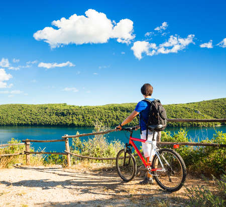 Rear View of a Man with a Bicycle on Beautiful Nature Background. Healthy Lifestyle and Travel Concept. Copy Space.
