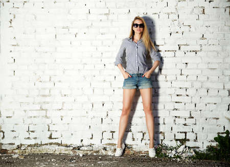 Full Length Portrait of Trendy Hipster Girl with Hands in Pockets on White Brick Wall Background. Trendy Urban Fashion Concept. Copy Space. Standard-Bild