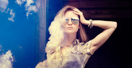 Double Exposure Portrait of Hipster Girl with Sunglasses over Sky and Clouds Background. Toned and Filtered Photo. Copy Space. photo