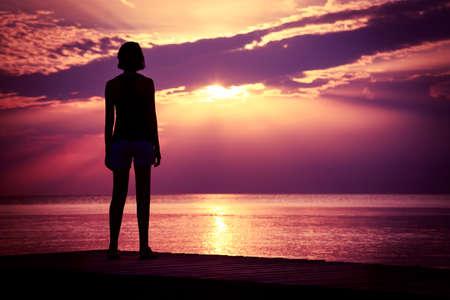 Silhouette de jeune femme regardant la mer Coucher de soleil. À couper le souffle Nature Background. Photo teintée avec Espace texte. Banque d'images