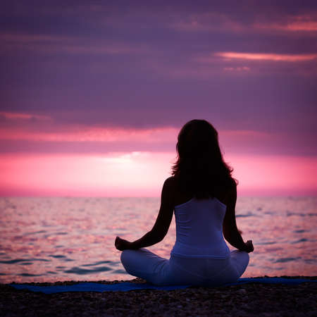 Silhouette of Woman Meditating in Lotus Position by the Sea at Sunset. Rear View. Nature Meditation Concept.