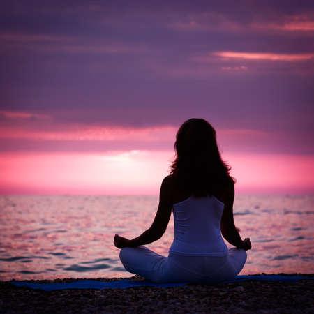 夕暮れ海で蓮華座に瞑想の女性のシルエット。後姿。自然の瞑想の概念。          写真素材