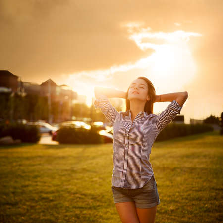Dreamy Woman Enjoying Life. City Sunset. Relaxation Concept. Toned and Filtered Photo. Copy Space. Stock Photo