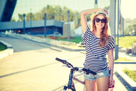 도시에서 자전거와 함께 행복 한 소식통 소녀입니다. 톤 및 필터링 사진. 현대 청소년 라이프 스타일 개념입니다.