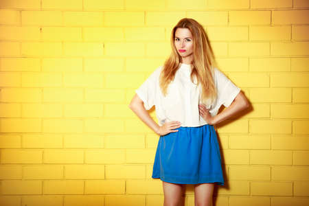 Portrait of Trendy Hipster Girl Making Duck Face with Hands on Hips. Yellow Brick Wall Background with Copy Space. Urban Fashion Concept.