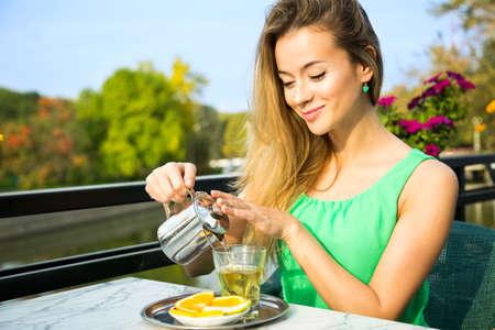 genießen: Glückliche lächelnde Frau, die grüne Tee im Freien. Summer Background. Gesunde Ernährung Konzept. Shallow Depth of Field.