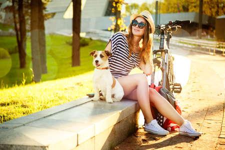 Lächeln Hipster Mädchen mit ihrem Hund und Fahrrad in der Stadt. Fit und Filtered Foto mit Bokeh und Kopie Raum. Städtische Jugend Lifestyle-Konzept.