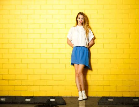 노란 벽돌 벽 배경에 서 그녀의 뒤에 손 소식통 패션 소녀의 전체 길이 초상화. 청소년 도시 패션 개념. 공간을 복사합니다. 스톡 콘텐츠