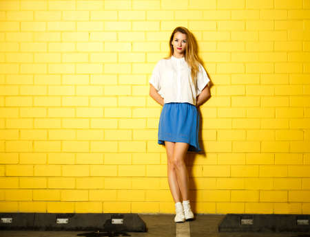 Full Length Portrait of Hipster Fashion Girl with Hands behind her Back Standing at the Yellow Brick Wall Background. Youth Urban Fashion Concept. Copy Space.