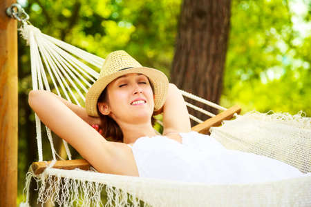 hands out: Happy Young Woman Relaxing in a Hammock and Smiling. Hands Behind Head. Summer Nature Daydreaming Concept.