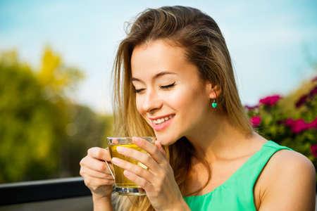 젊은 행복 한 여자 마시는 녹차 야외. 여름 배경입니다. 얕은 피사계 심도. 건강 한 영양 개념입니다.