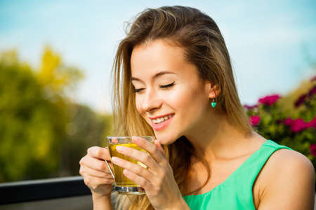 green field: Young Happy Woman Drinking Green Tea Outdoors. Summer Background. Shallow Depth of Field. Healthy Nutrition Concept.