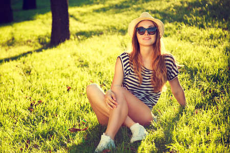 Happy Hipster Girl Relaxing on the Grass. Toned and Filtered Photo. Modern Youth Lifestyle Concept.