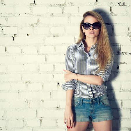 흰색 벽돌 벽 배경에 젊은 소식통 여자의 초상화입니다. 트렌디 한 캐주얼 패션 개념. 스트리트 스타일 의상.