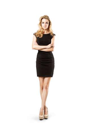 리틀 블랙 패션 드레스에 섹시한 금발의 여자의 전체 길이 초상화. 교차 팔과 다리. 닫힌 몸 자세. 신체 언어 개념. 흰색에 격리.