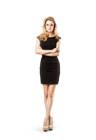 body language: Full Length Portrait of a Sexy Blonde Woman in Little Black Fashion Dress. Crossed Arms and Legs. Closed Body Posture. Body Language Concept. Isolated on White.