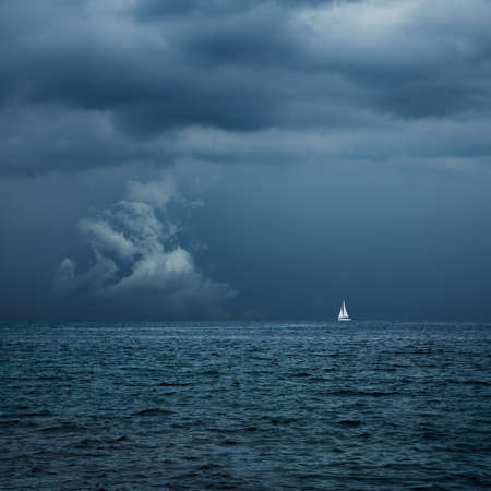horizons: Boat Sailing in Center of Storm Formation. Dramatic Background. Danger in Sea Concept. Toned Photo with Copy Space.