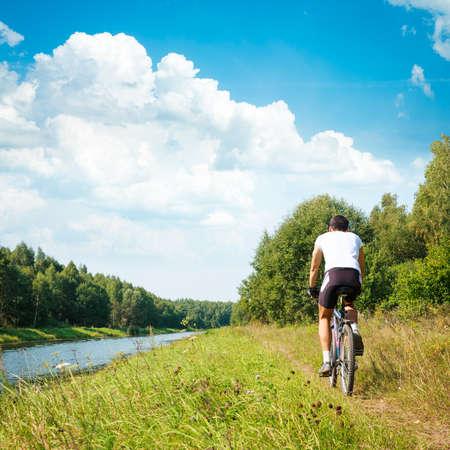 ciclista: Vista posterior de un Ciclista que monta una bici en la orilla del río. Estilo de vida saludable concepto. Foto cuadrada con espacio de copia.