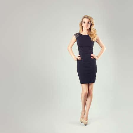 엉덩이에 손을 리틀 블랙 패션 드레스에 섹시한 금발 여자의 전체 길이 초상화. 회색 배경입니다. 신체 언어 개념입니다. 복사 공간 톤 인스 타 그램 스