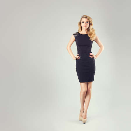 lenguaje corporal: Retrato integral de una mujer rubia atractiva en poca alineada Moda Negro con las manos en caderas. Fondo gris. Body Concept Idioma. Entonado Instagram Styled fotos con espacio de copia.