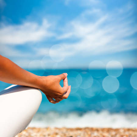 blue sky thinking: Yoga Hand on Sea Background. Healthy Lifestyle Concept. Beautiful Photo with Bokeh. Shallow Depth of Field.