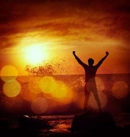 Silhouette of Man with Raised Arms against Stormy Sea over Dramatic Sunset. Motivation and Strength Concept. Filtered Photo with Bokeh.