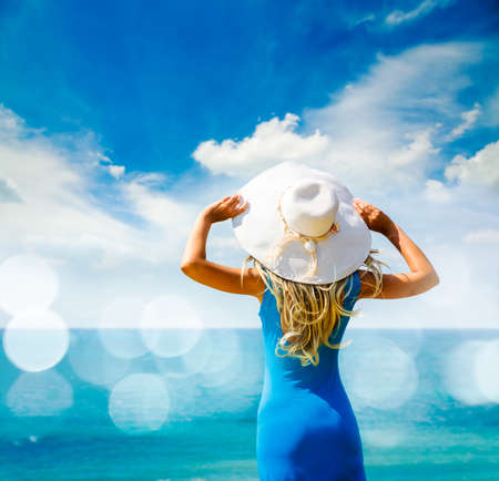 Blonde Woman in Blue Dress Standing at Sea and Holding White Hat. Back View. Summer Vacation Concept. Photo with Bokeh and Copy Space.