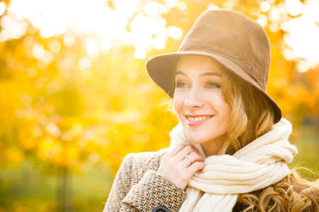 Fashion Woman in Hat on Autumn Background in Sunny Day. Smiling Happy Girl Portrait. Photo with Bokeh and Copy Space. Banque d'images