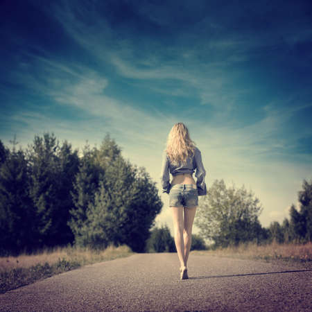 pantalones cortos: Longitud completa de la foto de la muchacha rubia atractiva Walking Away.