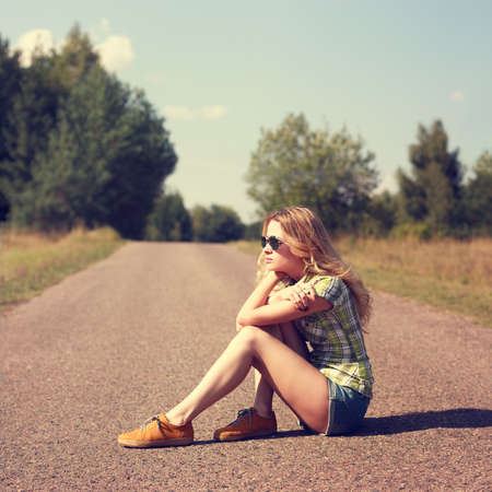 Street Style Fashion Woman Sitting on the Road Outdoors.  Modern Youth Lifestyle Concept. Standard-Bild