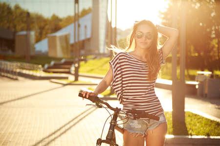 流行: 市内で自転車とファッション流行に敏感なティーンエイ ジャー。トーンとフィルターの写真です。現代の 10 代のライフ スタイルのコンセプトです