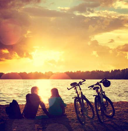 Romantisch Paar met Fietsen ontspannen bij zonsondergang aan het meer. Fall in Love Concept. Getinte foto met Bokeh.