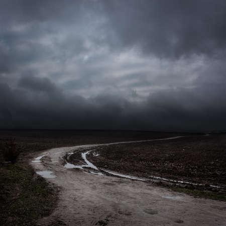 Nacht Landschap met landweg en donkere wolken. Moody Sky.
