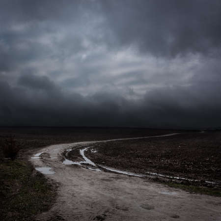 Night Landscape with Country Road and Dark Clouds. Moody Sky .