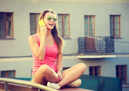 Happy Girl Talking by the Phone Outdoors. Modern Teenager Lifestyle Concept. Toned Photo with Copy Space. Stock Photo