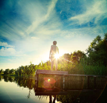 Young Man Standing on the Pier by Lake. Summer Nature Background. Recreation Concept. Toned Photo with Lens Flare.