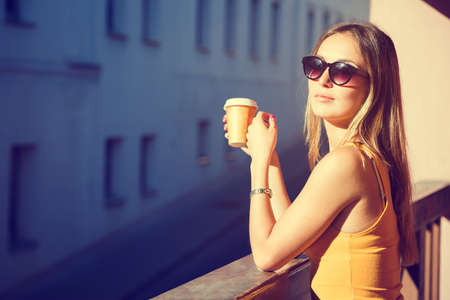 Beautiful Woman with Coffee to Go in the City. Toned Photo with Copy Space.