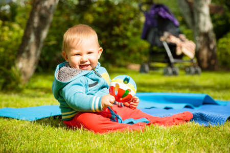 Portrait of Happy Baby Playing with Ball Outdoors. Summer Green Background. Copy Space.