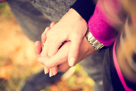 Closeup Hands of a Couple Held Together on Autumn Background. Toned Photo with Shallow Depth of Field. Focus on Ring.