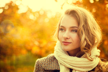 Portrait of Young Fashion Woman Outdoor on Autumn Background. Toned Photo with Bokeh and Copy Space. Stock Photo